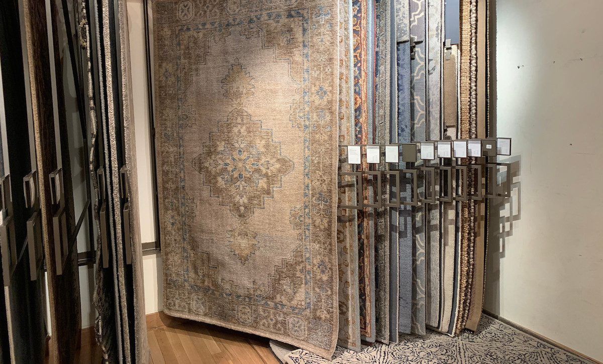 row of rectangular patterned rugs hanging on racks in a store