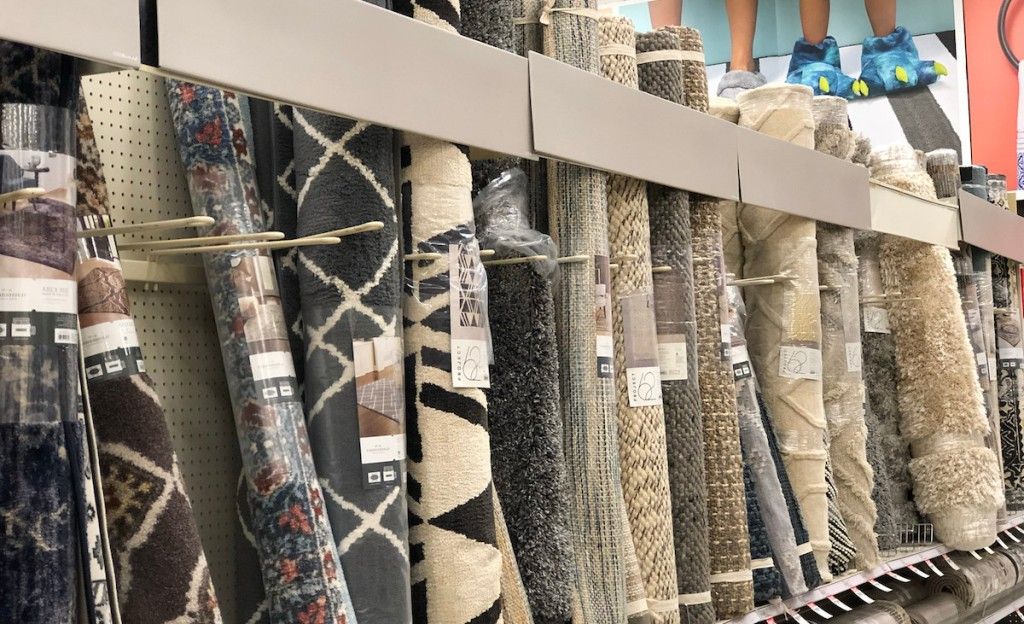 row of standing rolled up rugs on a store shelf