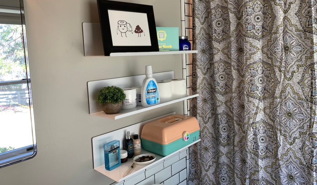 white metal wall shelves in a bathroom next to medallion shower curtain