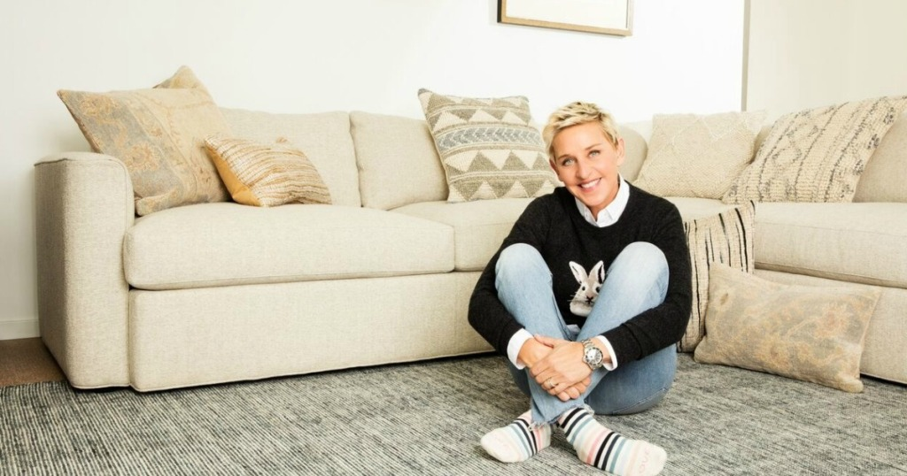 ellen degeneres smiling sitting on striped rug in living room