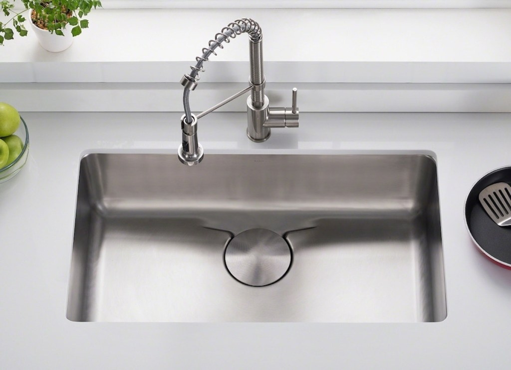 stainless steel sink with chrome faucet and white countertops