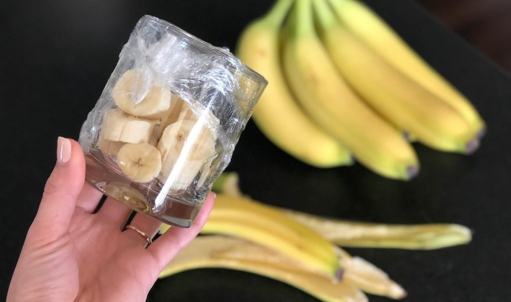 hand holding sliced banana in a glass covered with plastic wrap with bananas in the background