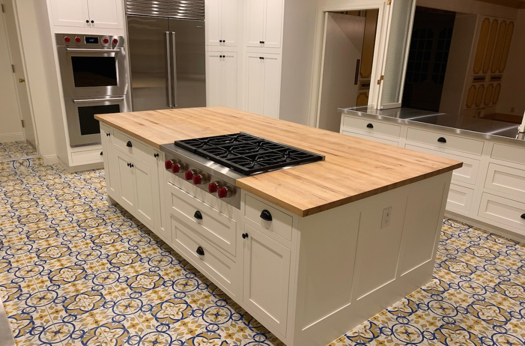 large butcher block island with stainless steel range red knobs white cabinets and mexican style tile floor