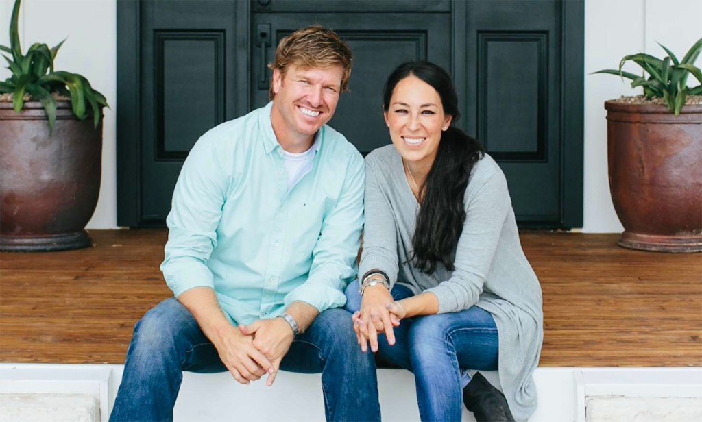 chip and joanna gaines sitting next to each other smiling on porch steps