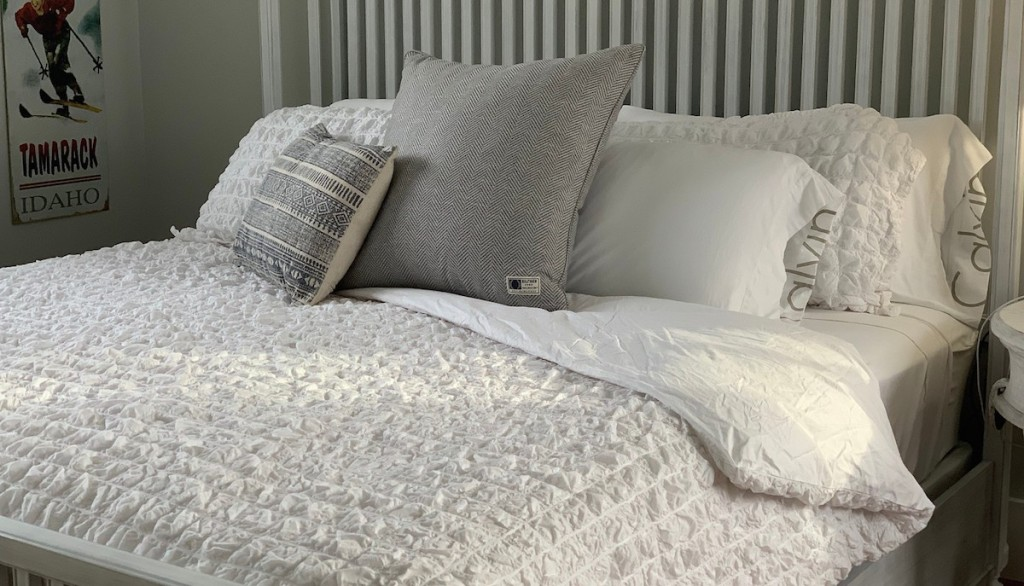 white and gray bedding on white framed bed in room with pillows