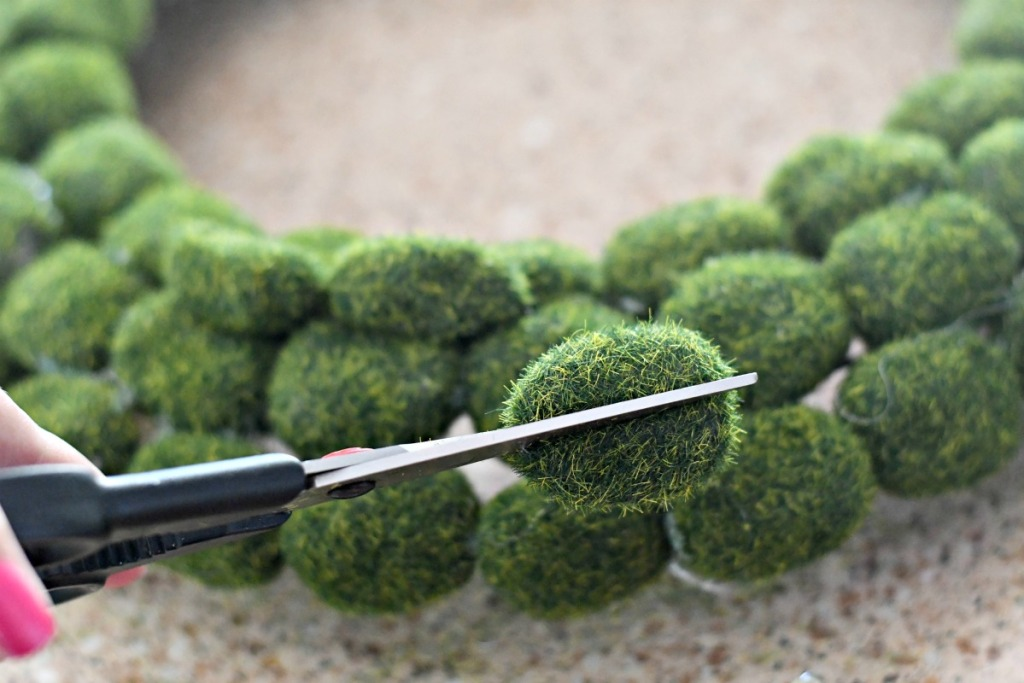 easy way to make a dollar tree moss rock wreath by cutting them in half using scissors