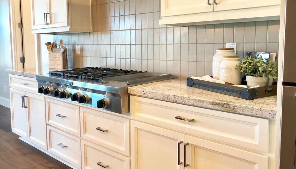 cream colored kitchen cabinets stainless steel range with black knobs and granite stone counters