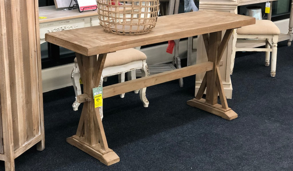 natural colored wood console table with basket on top sitting in store
