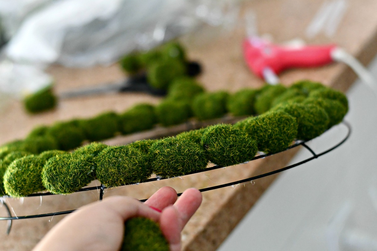 closeup of the moss wreath from the side as it's attached to the wire frame