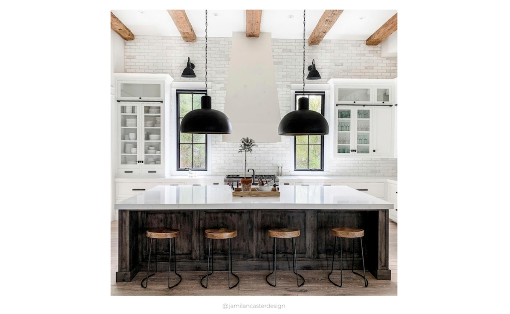 square photo of black and white kitchen with large pendants beams on ceiling and kitchen stools