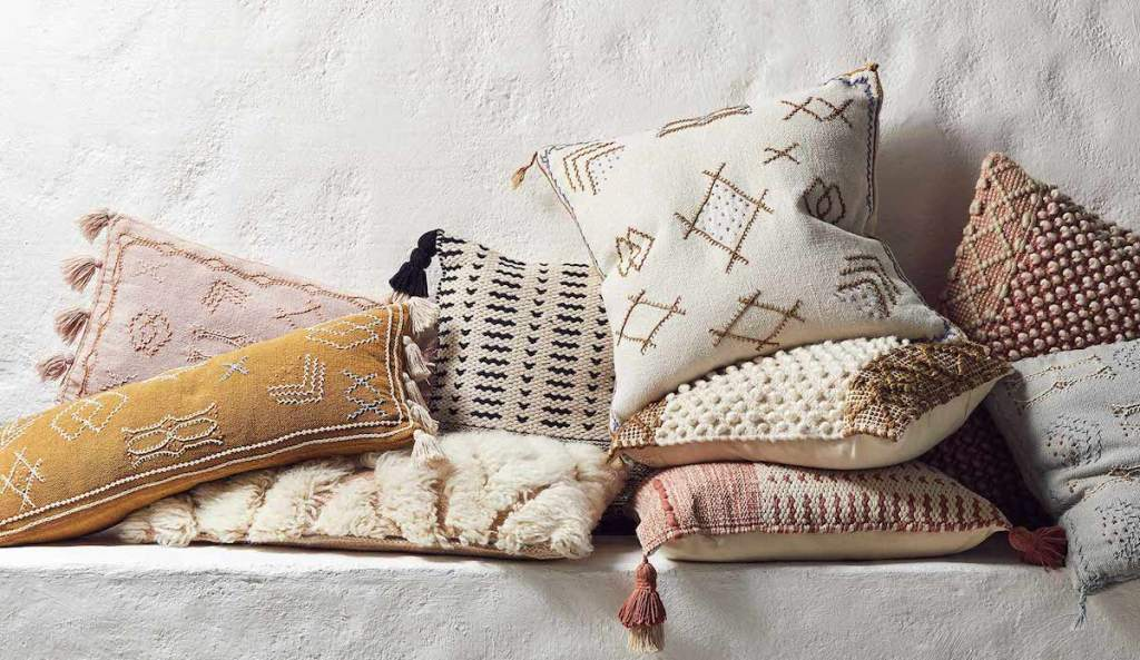 neutral muted tones on textured global inspired pillows sitting on concrete wall