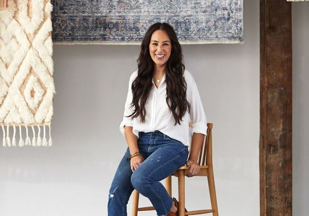joanna gaines sitting on stool with hanging rugs in the background