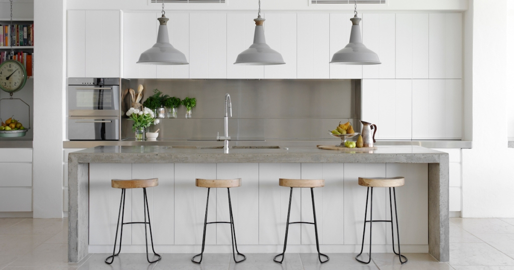 modern white and silver kitchen with four barstools and white pendant lights