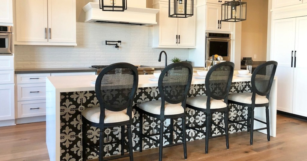 kitchen with white cabinets and black oval stools