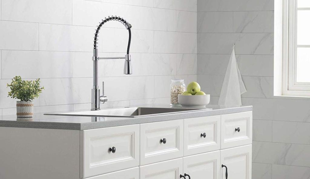 chrome spring faucet with white tile backsplash white cabinets and gray countertops