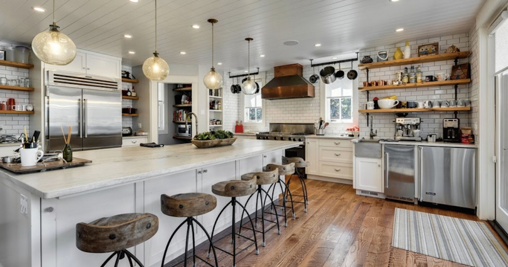 huge white kitchen with copper range hood and wood and iron barstools lined up at island counter