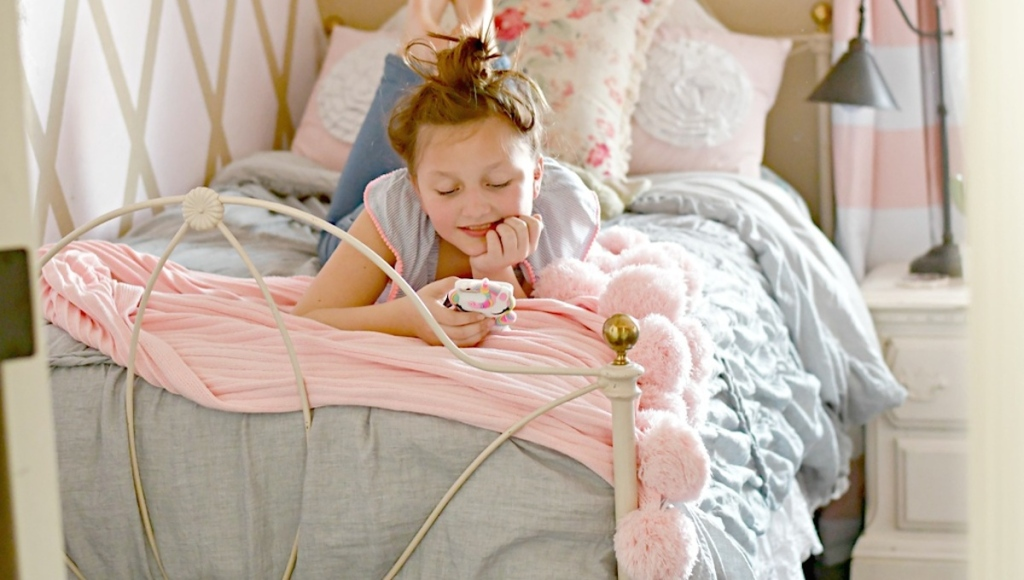 teen girl laying on bed with gray duvet and pink pom blanket