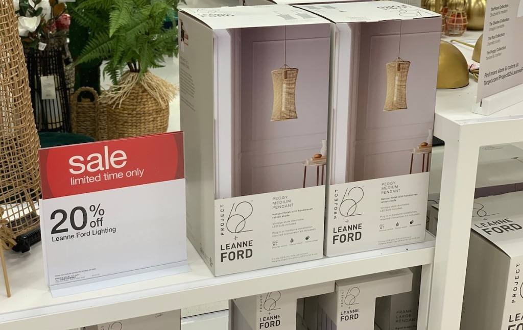 two boxes in store of woven natural colored pendant lights next to sale sign