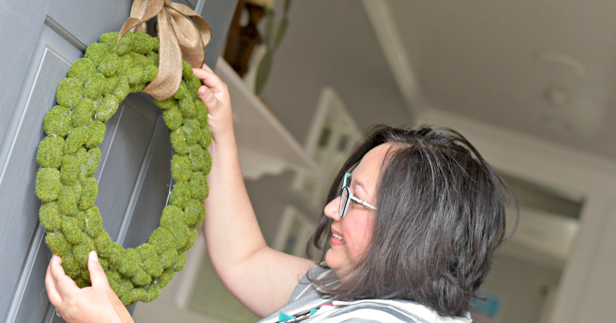 Lina hanging the moss wreath on her front door