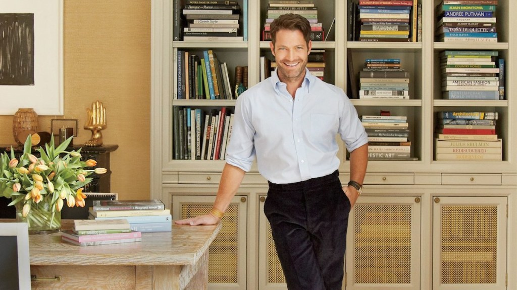nate berkus standing in front of home library with tons of book