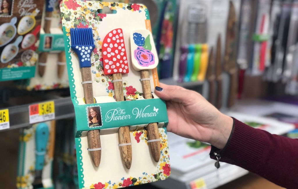 hand holding set of colorful rubber spatulas in store aisle