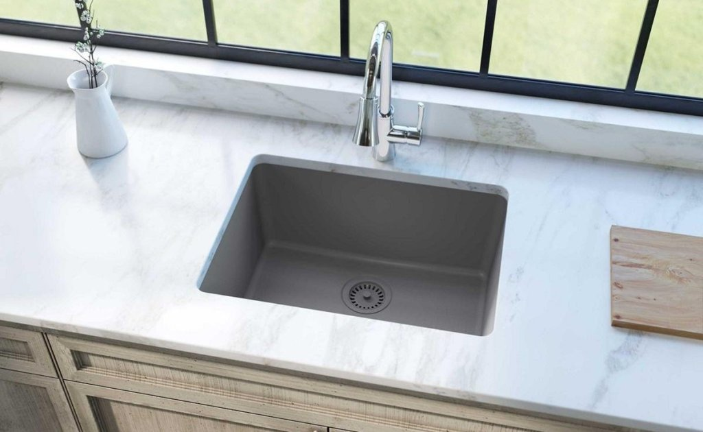 gray colored undermount sink with chrome faucet marble countertops and beige cabinets