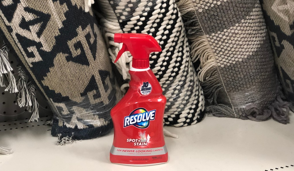 red spray bottle of resolve sitting on a metal shelf with black and cream rugs in background