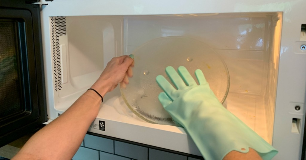 Cleaning microwave with kitchen glove