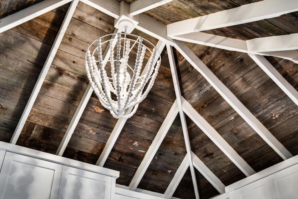high ceiling with white painted beams and brown wood throughout with white beaded chandelier hanging in the middle