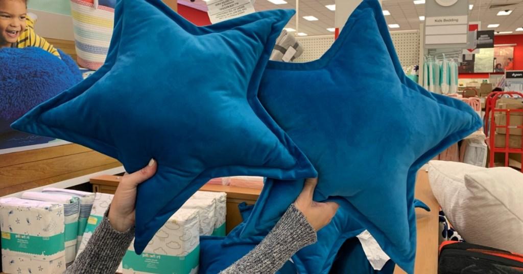 holding Pillowfort star throw pillows