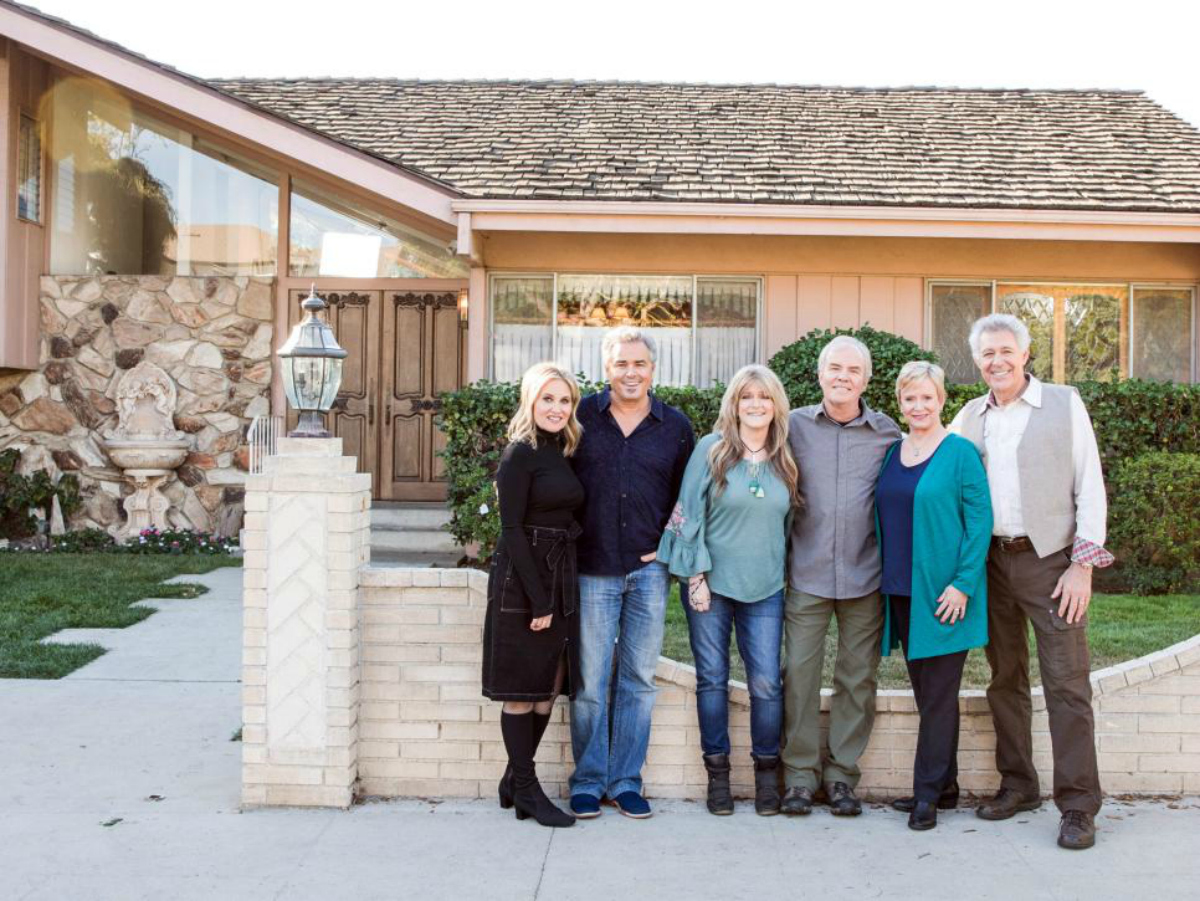 The Original Brady Bunch Crew standing outside of the house