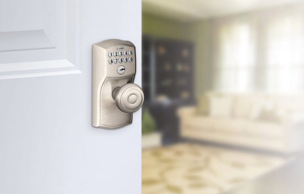 silver door knob and keypad lock on white door with living room blurred in background
