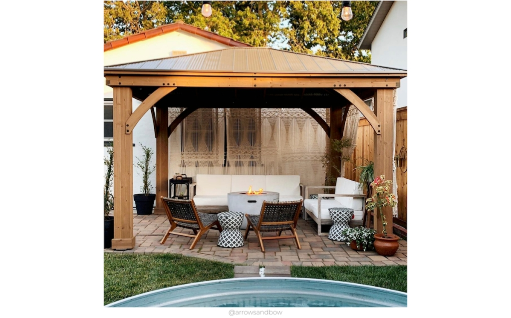 gorgeous cozy outdoor space with furniture and cement firepit and accent chairs