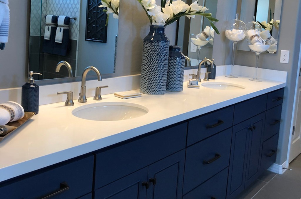 bathroom double vanity with navy blue cabinets and white countertops with flowers
