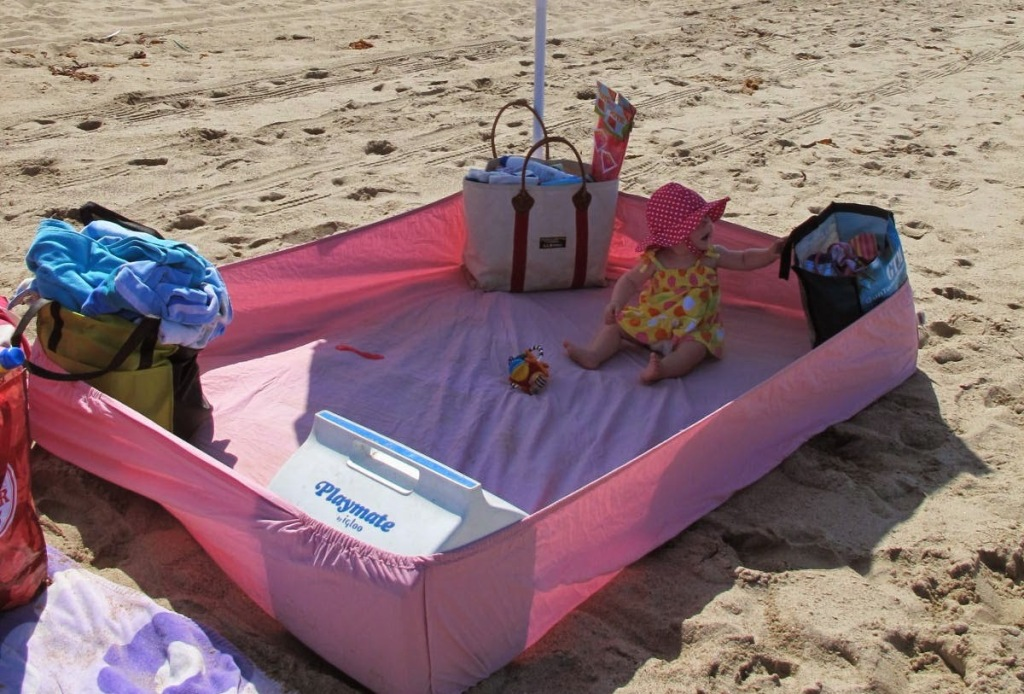 pink fitted sheet in sand with cooler beach bags and baby sitting inside