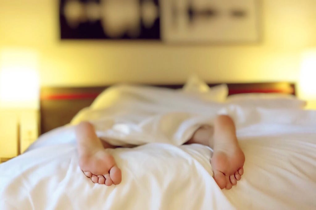 feet sticking out of white bed sheets