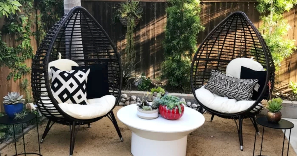 two black teardrop shaped chairs outside on a patio