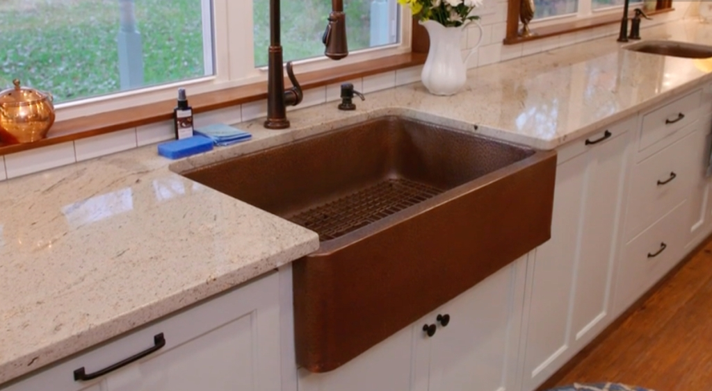 copper apron sink with white cabinets and granite stone countertop below window