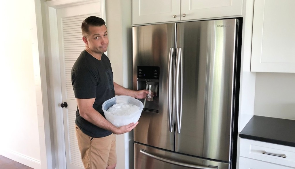disappointed man holding glass and bucket of ice in front of stainless steel fridge