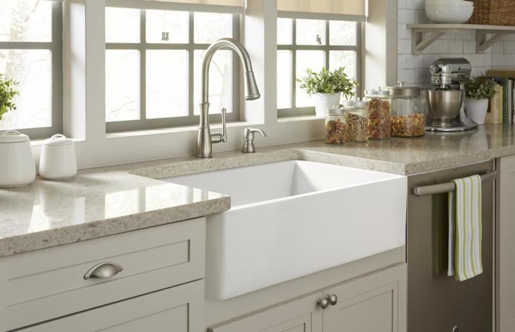 white apron sink with stainless steel faucet cream gray cabinets and stone countertops below large window