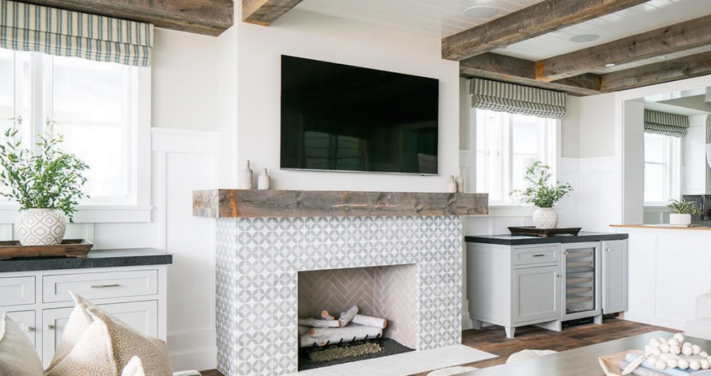 black TV over fireplace with salvaged wood mantel and decor