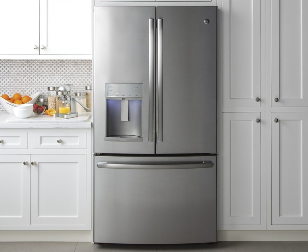 stainless steel french door fridge with white shaker kitchen cabinets surrounding it