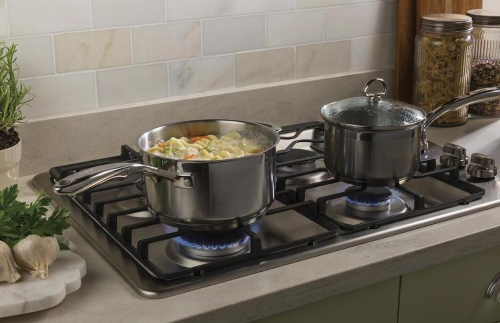 gas range with two stainless steel pots with noodle soup boiling with tile backsplash