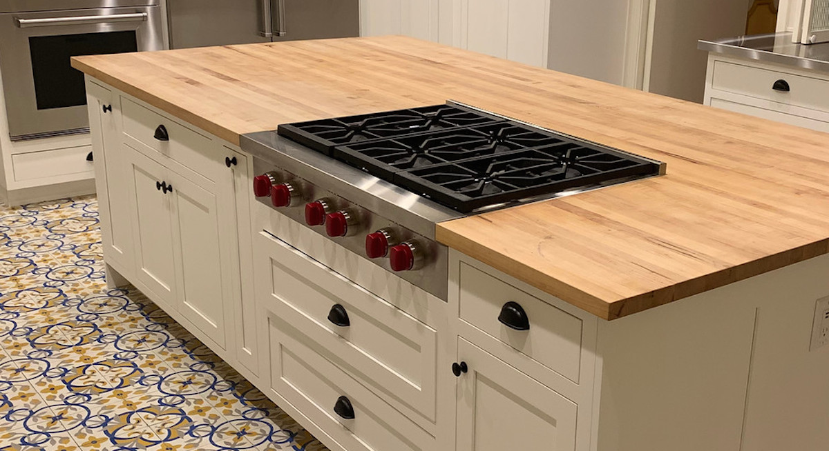 wolf gas stainless steel cooktop with red knobs on butcher block countertop white cabinets