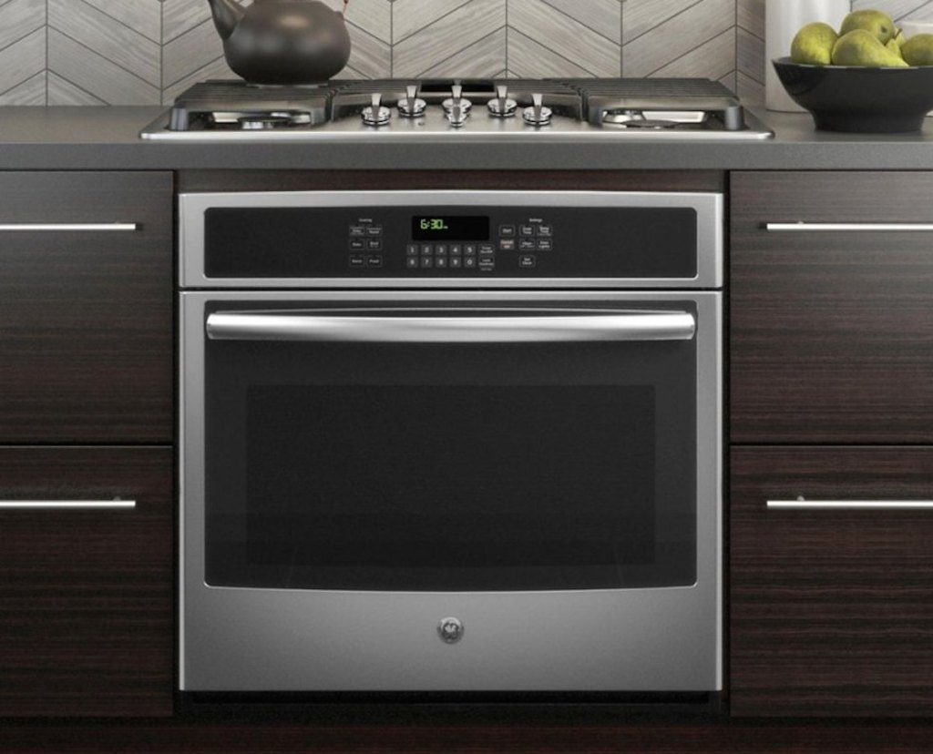 stainless stell oven with dark brown modern cabinets range on counter and tea kettle on top