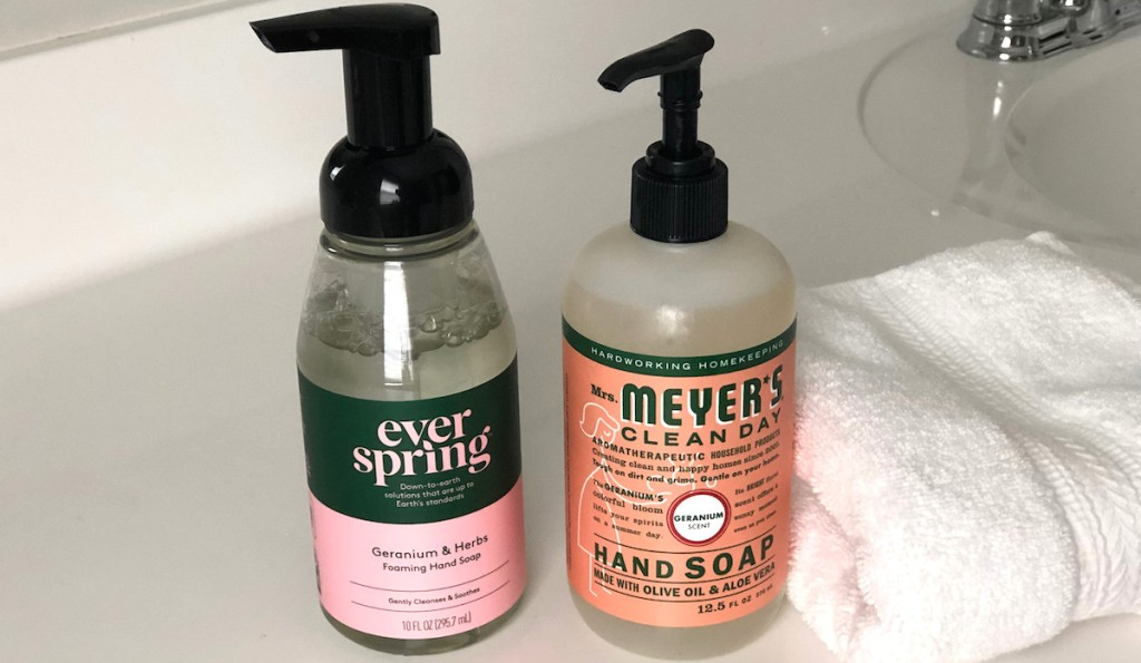 everspring pink geranium soap next to orange mrs meyers bottle with white towel on white countertop