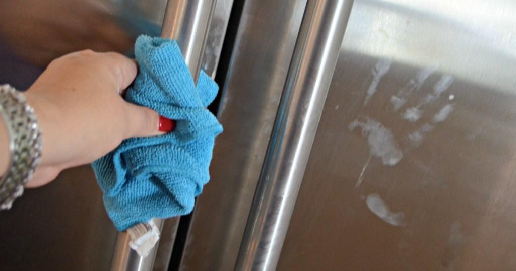 hand washing fridge hand prints with blue towel