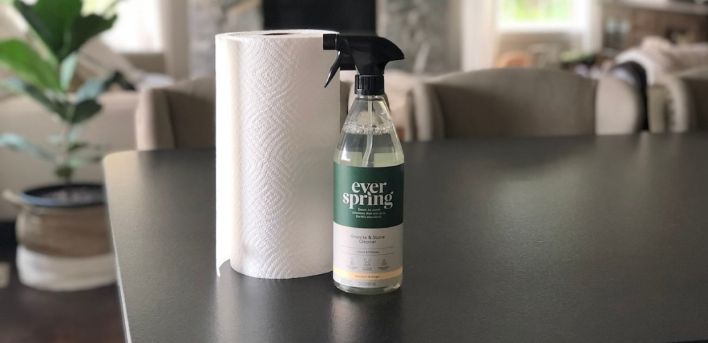 white roll of paper towels on black countertop next to bottle of gray everspring granite and stone cleaner