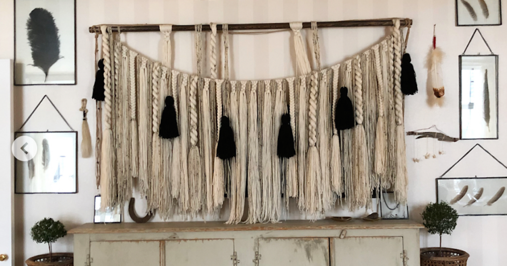 large macrame banner garland hanging on wall with black tassels and console table below