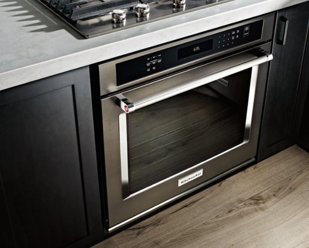 stainless steel kitchenaid oven with black cabinets and gray countertops